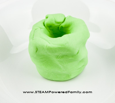 Erupting Slime - A Saline Slime STEM Activity that incorporates the traditional volcano science experiment kids love, with a new slime twist.