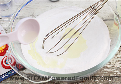 Adding bath bomb ingredients to a bowl and whisking them together.
