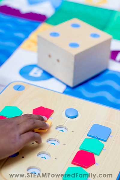 Boy placing coding blocks in the Cubetto board with Cubetto Robot ready to launch in the background.