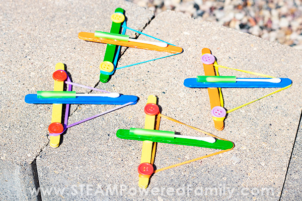 A variety of colours of the launcher a kid made STEAM craft from popsicle sticks