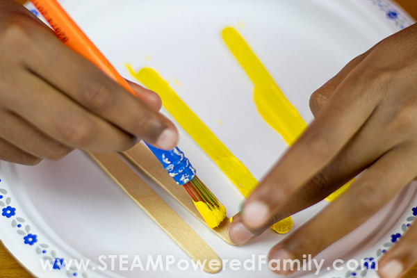Painting crafts sticks is the first step in this STEAM inspired craft sticks project to build a launcher
