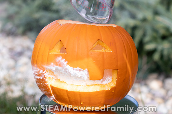 Careful pouring the baking soda into the pumpkin volcano