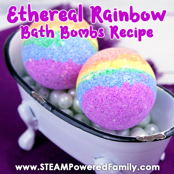 On a purple towel is a miniature antique clawfoot bathtub, white with a black, chipped lip. Inside it is filled with pearl beads on which sit two bath bombs in layered colours of the rainbow. Overlay text says Ethereal Rainbow Bath Bombs Recipe.