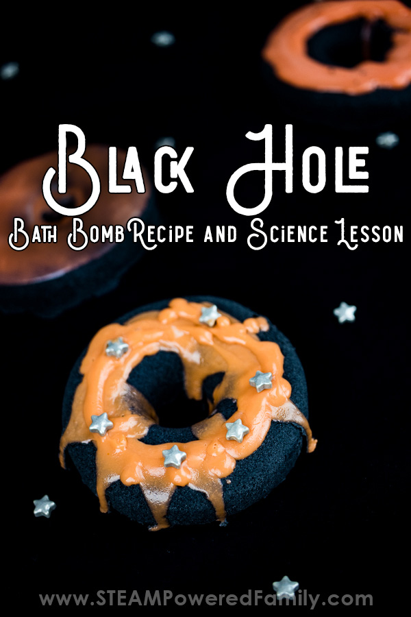 Black hole bath bombs on a black background. Black donut shaped bases with orange soap rings on top. 3 bath bombs pictured with text overlay that says Black Hole Bath Bomb Recipe and Science Lesson