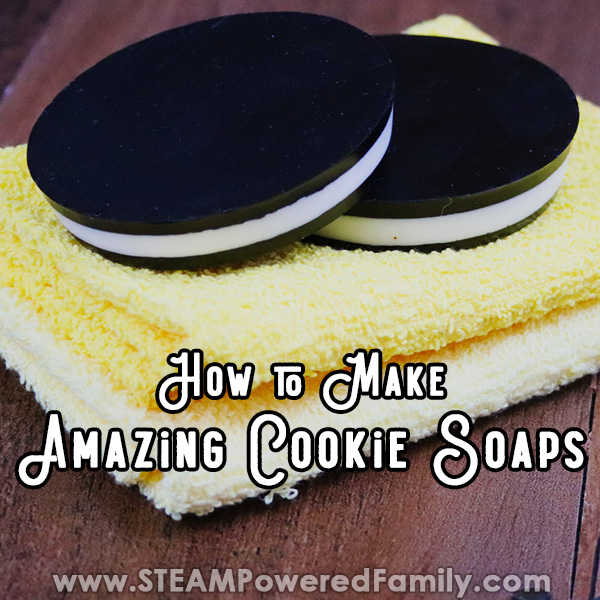 On a wood background sits a folded white towel beneath a folded yellow towel. On top of the towels perches two soaps that look like cookies with outer black layers and a white middle layer. Overlay text says How to Make Amazing Cookie Soaps