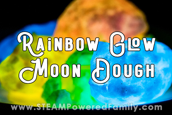 On a black background irregular shaped balls of moon dough are glowing orange, blue, green and yellow. Overlay text says Rainbow Glow Moon Dough