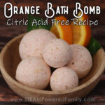 A wood bowl sits on a dark wood background. In the bowl is a pile of 5 bath bombs and some slices of orange. Overlay text says Orange Bath Bomb Citric Acid Free Recipe