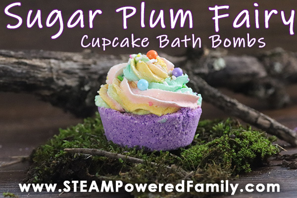 Sugar Plum Fairy Bath Bombs set on a woodland type setting with branches and moss. The Cupcake Bath Bomb is purple with multiple colours in the whipped icing soap topper which has colourful sprinkles.
