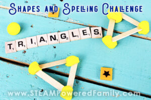 On a teal blue wood slate background sits Scrabble letter tiles spelling out the word TRIANGLES. Above and below it sits a triangle shape made out of craft sticks and yellow play dough. Overlay Text says Shapes and Spelling Challenge