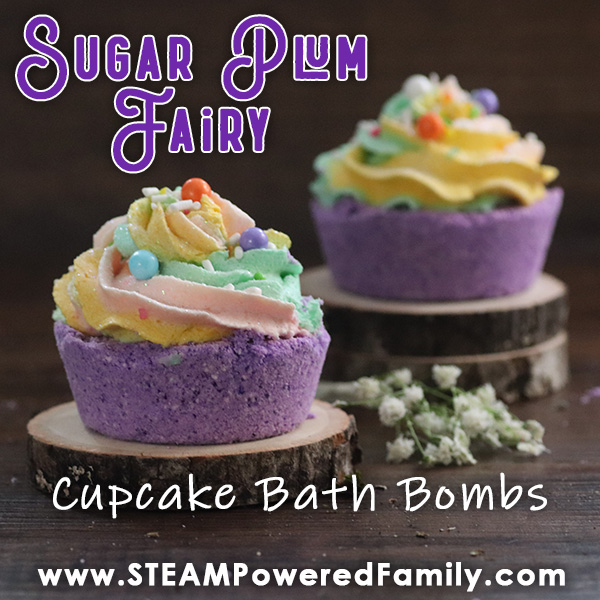 On a dark wood background sits two tree slices. Between the slices are small white flowers. On the slices are purple cupcake shaped bath bombs with whipped icing soap toppers in pink, yellow and green. Overlay text says Sugar Plum Fairy Cupcake Bath Bombs