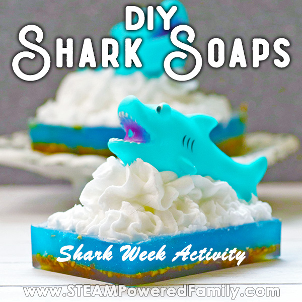 Two soaps with a dark base, blue middle, and white frothy waves with a shark cresting out of the waves. Overlay text says DIY Shark Soaps Shark Week Activity