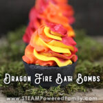 Black cupcake bath bombs with fire red orange and yellow whipped soap toppings sit on a bed of moss. Overlay text says Dragon Fire Bath Bombs