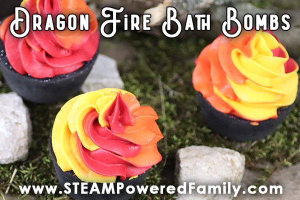 black cupcake bath bombs with red orange and yellow whipped soap topping in a forest like setting with moss, rocks and twigs.