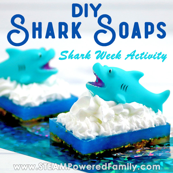 On a white background with a glittery turquoise foil strip sits two soaps with a dark base, blue middle, and white frothy waves with a shark cresting out of the waves. Overlay text says DIY Shark Soaps Shark Week Activity