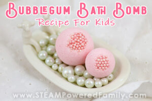Pink bath bombs sit in a small antique bath tub with overlay text saying Bubble Gum Bath Bombs Recipe For Kids