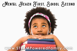 Child resting her chin on a stack of books Mental health first, school second